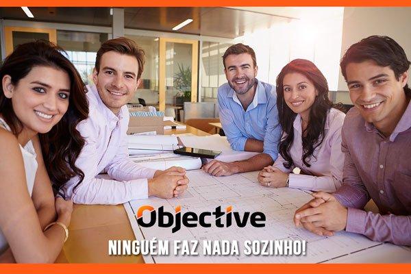 equipe de cinco pessoas em uma mesa olhando para a foto e com um papel com a estratégia desenhada