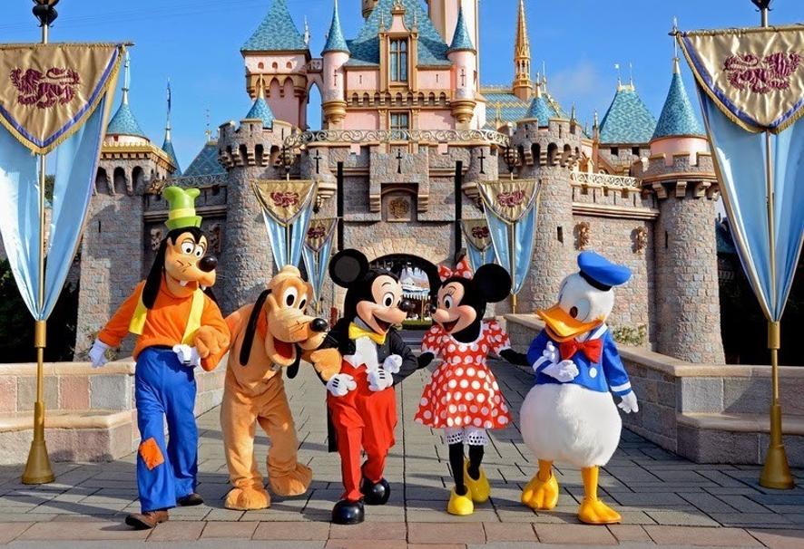 imagem do castelo da Disney com os personagens pluto pateta, mickey, minnie e pato donald na frente