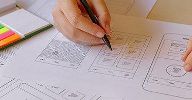 Mão desenhando uma interface de aplicativo com lápis