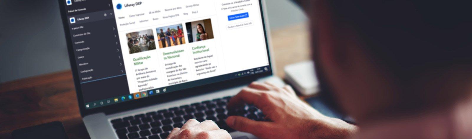 Pessoa utilizando o computador com portal e CMS da Liferay (Liferay DXP)