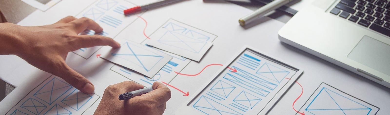 Pessoa desenhando protótipo de aplicativo em papel