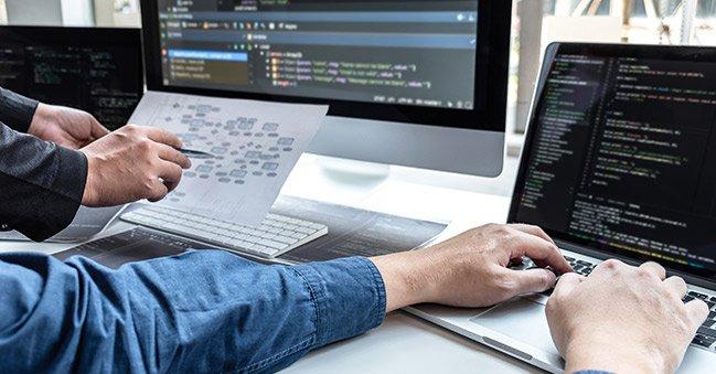 Pessoa utilizando o computador para realizar o desenvolvimento de software