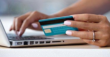 Mulher digitando em computador segurando cartão de crédio