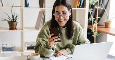 Jovem em escritório informal sentada em frente ao computador e utilizando o celular