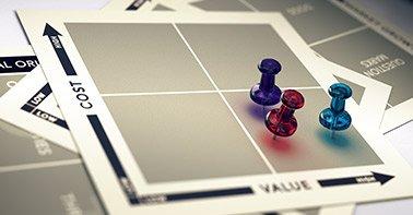 """Imagem de alguns alfinetes sobre um papel escrito """"Cost"""" e """"Value"""""""