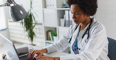 Médica utilizando o computador
