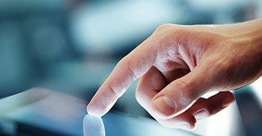 Mão tocando uma tela interativa