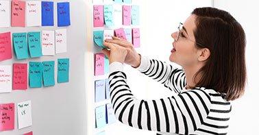 Mulher colocando post-its coloridos na parede