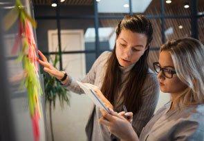 duas mulheres conversando olhando para um caderno e apontando para post-its colados na parede